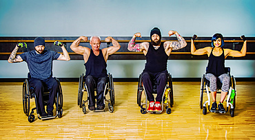 A group of paraplegic friends fooling around showing their muscles after a workout in fitness facility: Sherwood Park, Alberta, Canada