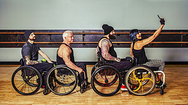A group of paraplegic friends fooling around after a workout in fitness facility and taking a self-portrait of their wheelchair train: Sherwood Park, Alberta, Canada