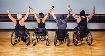 A view from behind of a group of paraplegic friends holding their hands high in a victory celebration after a workout in fitness facility: Sherwood Park, Alberta, Canada