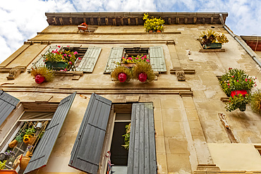 House with shutters and floral hanging baskets; Arles, Provence, France