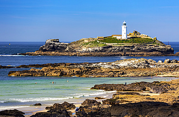 White Godrevy Lighthouse on rock formation in blue water with blue sky and rocky shoreline, Godrevy Island in St. Ives Bay; Cornwall County, England