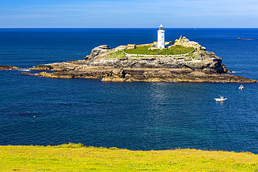White Godrevy Lighthouse on rock formation in blue water with blue sky, Godrevy Island in St. Ives Bay; Cornwall County, England
