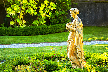 Stone female statue in garden with pebble pathway, framed by stone wall and trees; Cornwall County, England