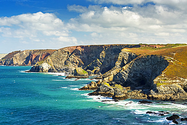Rocky cliffs along the shoreline with clouds and blue sky; Cornwall County, England