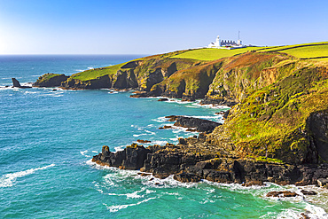 White lighthouse on top of hilly green fields framed by rocky outcrops and blue sky; Cornwall County, England