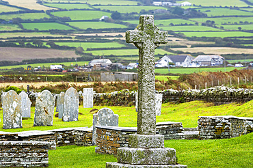 Old stone cross gravestone in graveyard with patchwork of fields in the background; Cornwall County, England