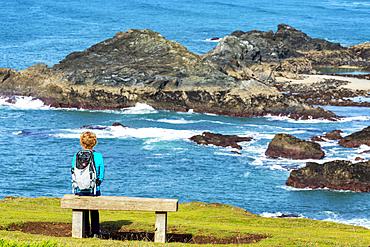 A female hiker sitting on a wooden bench overlooking rocky shoreline; Cornwall County, England