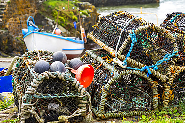 Close-up of lobster and crab cages stacked up, with fishing boat in the background; Cornwall County, England