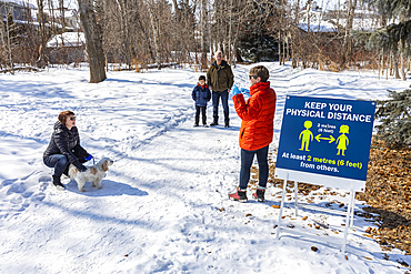 Families stand to visit at a distance on a path through a park during the Covid-19 world pandemic; St. Albert, Alberta, Canada