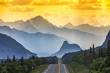 Glenn Highway divides the image, surrounded by spruce forest and brush in Southcentral Alaska, at sunset, with cars in the distance looking towards Lion's Head and the Chugach Mountains on a smokey, hazy, summer night; Chickaloon, Alaska, United States of America