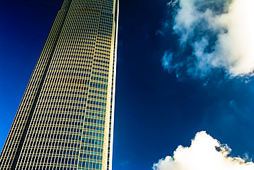 Architectural detail of a skyscraper with blue sky and white clouds; Hong Kong, Hong Kong Special Administrative Region (SAR), Hong Kong