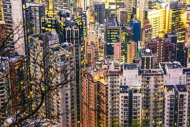Crammed Hong Kong apartment blocks at dusk; Hong Kong, Hong Kong Special Administrative Region (SAR), Hong Kong