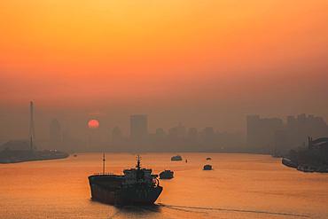 Misty sunrise on a river in China; Shanghai, Shanghai, China