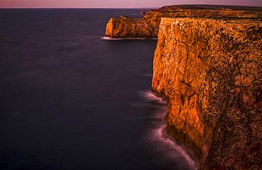 Long exposure of Portuguese cliffs at dusk at the most southwestern tip of Europe, Cape St. Vincent; Sagres, Algarve, Portugal