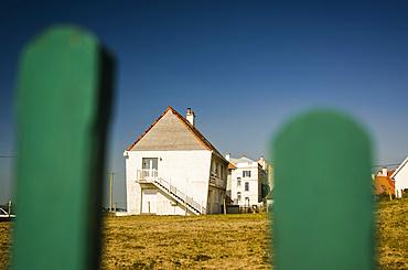 White house seen through green fence posts in Northern France; Ambleteuse, Pas de Calais, France