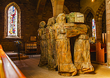 View from behind of a carved wooden statue depicting monks bearing the coffin of St. Cuthbert on their shoulders in the Lindisfarne Priory: Holy Island, Northumberland, England