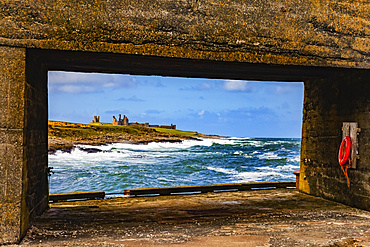 View Of Dunstanburgh Castle from a pier with a cement structure on Craster Harbour; Craster, Northumberland, England