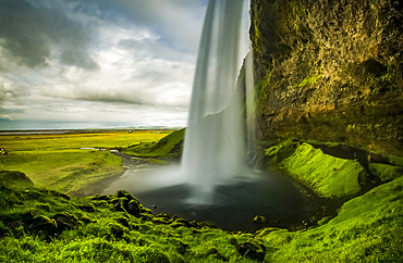 View of a rushing waterfall taken from behind, Seljalandsfoss; Iceland