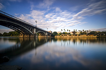 Reflection of a river and Guadalquivir bridge at dusk; Seville, Andalucia, Spain