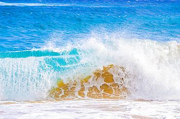 Splashing waves along the shore of golden sand; Oahu, Hawaii, United States of America