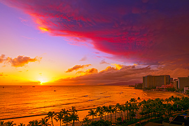 Waikiki Beach in vibrant colours at sunset with a dramatic glowing cloud formation overhead; Honolulu, Oahu, Hawaii, United States of America