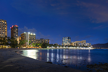 Waikiki at sunset, with illuminated buildings and tranquil waterfront; Honolulu, Oahu, Hawaii, United States of America