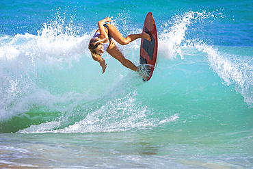 A young woman riding a wave on a skimboard off Sandy Beach, Oahu; Oahu, Hawaii, United States of America
