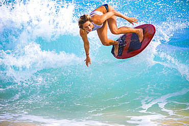 A young woman leaps in the air on a skimboard off Sandy Beach, Oahu; Oahu, Hawaii, United States of America