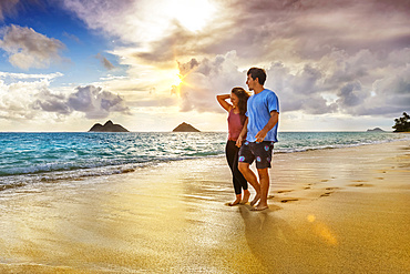 A couple walks on Lanakai beach on the Hawaiian island of Oahu at sunset; Lanakai, Oahu, Hawaii, United States of America