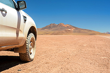 Four-wheel drive vehicle seen from the side and showing off-road tire with high altitude desert and mountains in the background; Potosi, Bolivia