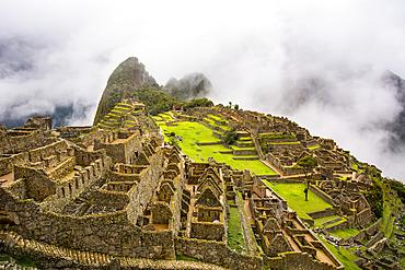 The sacred city of Machu Picchu sunlit and enveloped in low clouds; Cusco, Peru