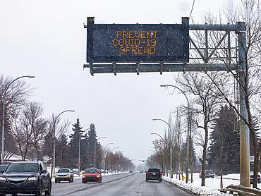 Road sign reading 'Prevent Covid-19 Spread'; Edmonton, Alberta, Canada