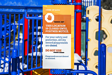 A sign at a playground cordoned off with caution tape during the COVID-19 World Pandemic; Edmonton, Alberta, Canada