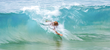 A man swims in the crest of a turquoise wave; Kihei, Maui, Hawaii, United States of America