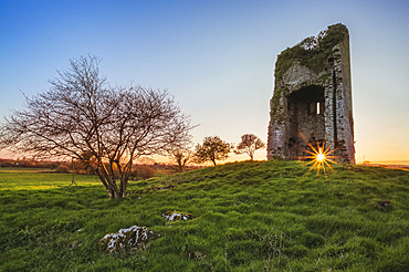 Old Irish castle ruins in a green field with the setting sun coming through the window hole; Clonlarra, County Clare, Ireland