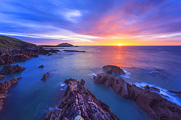 Sun rising over the Irish coastline with jagged rocks in the foreground and a lighthouse on an island in the distance; Ballycotton, County Cork, Ireland