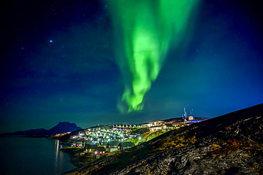 Northern Lights over the glowing city of Nuuk; Nuuk, Sermersooq, Greenland