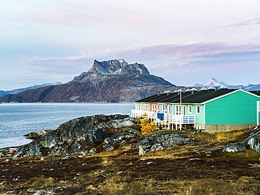 Colourful houses with decks on the back and mountains long the coastline; Nuuk, Sermersooq, Greenland