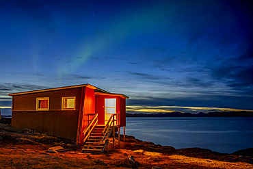 A small house on the water's edge with a view of the tranquil coastline at nightfall and the glowing northern lights above; Nuuk, Sermersooq, Greenland