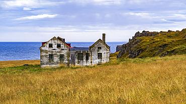A weathered and abandoned house along the coast; Iceland