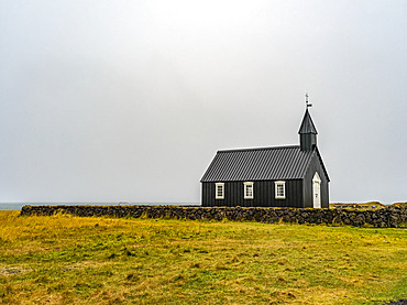 Church building with steeple and cross in a remote area with stone wall and grass; Snaefellsbaer, Western Region, Iceland