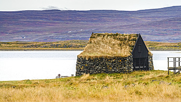 Stone building with grass roof facing the fjord, and a cross in the grass in front; Sudavik, Westfjords, Iceland
