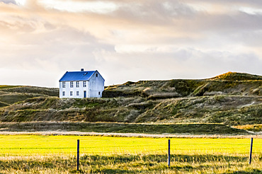 White house on grass knoll in Southern Iceland; Myrdalshreppur, Southern Region, Iceland