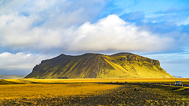 A rugged outcrop covered in green tundra with a road running through the vast landscape; Iceland