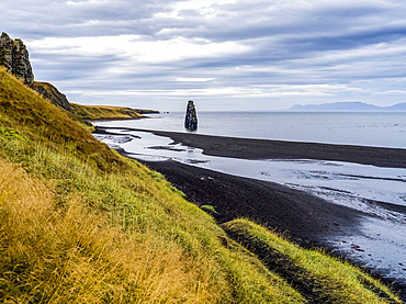 Tall rock formation and grassy slopes along the shoreline of a fjord; Iceland