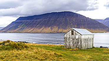 Weathered structure on the water's edge of a fjord in Northwestern Iceland in the municipality of Isafjarourbaer; Isafjarourbaer, Westfjords Region, Iceland