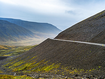 Road going around a bend on a hillside with a view of a valley and mountains under an overcast sky; Westfjords, Iceland