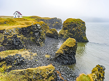 Rugged coastline of the Snaefellsnes Peninsula with a lone house along the cliffs in the mist; Snaefellsbaer, Western Region, Iceland