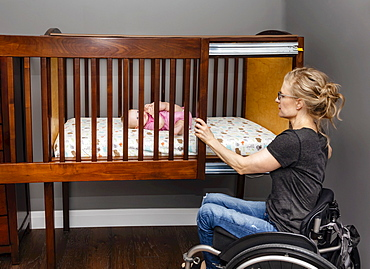 A paraplegic mom putting her baby down to sleep in a customized crib with a sliding door; Edmonton, Alberta, Canada