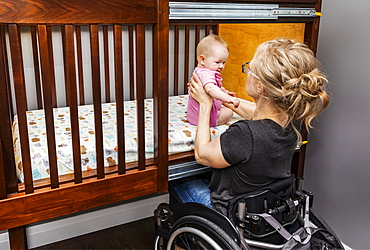 A paraplegic mother picking her baby up after a sleep in a customized crib with a sliding door; Edmonton, Alberta, Canada